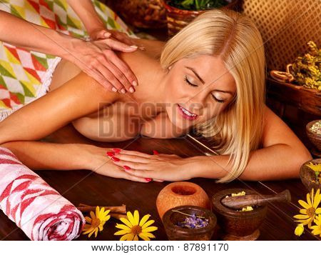 Woman getting back massage in tropical spa.