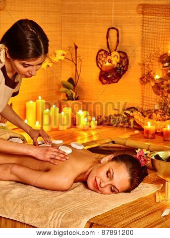 Blond woman getting by candlelight massage in spa.