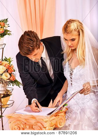 Groom and bride register marriage. Wedding indoor.