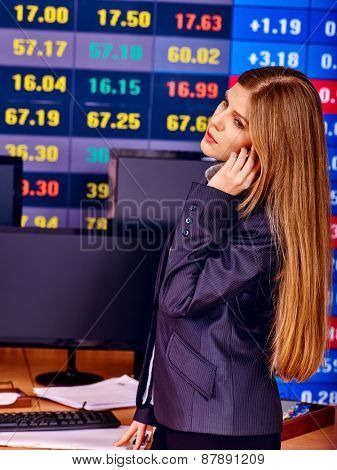 Business woman with  stock exchange board in office.
