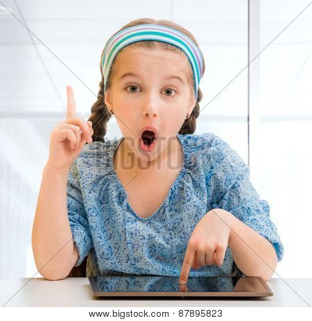 Happy little girl with her  tablet isolated on white