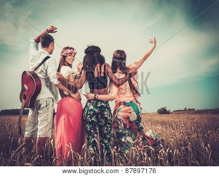 Multinational hippie friends with guitar in a wheat field