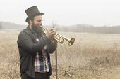 stock photo of gypsy  - Stylish bearded gypsy plays trumpet on a wilderness path - JPG