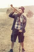 foto of gypsy  - Stylish bearded gypsy plays trumpet on a wilderness path - JPG