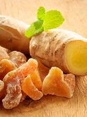 stock photo of home remedy  - Closeup dried candied crystallized ginger pieces and raw root on wooden table - JPG