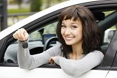 stock photo of car-window  - Pretty female driver in a white car showing the car key - JPG