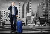 image of crossroads  - Man with baggage speaking by phone on the crossroad  - JPG