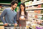 pic of supermarket  - Young couple choosing food in a supermarket - JPG