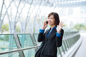 picture of waving hands  - Cheerful young business lady calling on the phone and waving her hand - JPG
