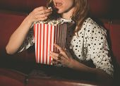 stock photo of watching movie  - A young woman is watching a movie and is eating popcorn at the cinema - JPG