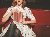picture of watching movie  - A young woman is watching an exciting movie and is eating popcorn at the cinema - JPG