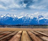 stock photo of bavarian alps  - Wooden planks floor with Bavarian Alps countryside lake landscape in background - JPG