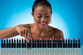foto of lipstick  - Beautiful smiling young woman choosing lipstick color