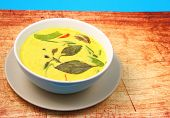 stock photo of curry chicken  - Hot and spicy chicken green curry on a blue background on a wood table top - JPG