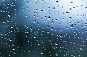 stock photo of rainy weather  - rainy weather water drops on a window pane blue background - JPG
