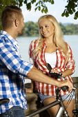 Happy blonde smiling caucasian woman meeting man on bicycle at the riverside outdoor. Looking at eac poster
