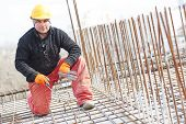 image of millwright  - construction worker portrait during reinforcement work with metal rebar rods at building site - JPG