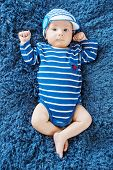 foto of knitted cap  - cute newborn baby in knitted cap on a blue background - JPG