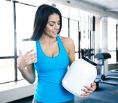 picture of containers  - Happy young woman holding plastic container with sports nutrtion at gym and looking on container - JPG