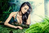 picture of rainforest  - Beautiful slim girl sitting by the pond in the rainforest - JPG