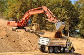 stock photo of track-hoe  - Large track hoe excavator filling a dump truck with rock and soil for fill at a new commercial development road construction project - JPG