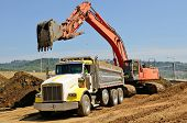 stock photo of excavator  - Large track hoe excavator filling a dump truck with rock and soil for fill at a new commercial development road construction project - JPG