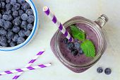 stock photo of masonic  - Blueberry smoothie with mint in mason jar glass with straw - JPG