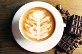 picture of latte  - Cup of coffee latte art with grains and chocolate on wooden table - JPG