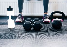 foto of crossed legs  - Closeup image of a woman sitting at gym with dumbbells - JPG