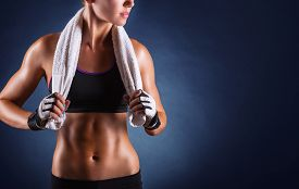 image of shoulder muscle  - Young sports woman after workout with towel on his shoulders on a dark background - JPG