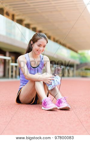 Sporty Woman listen to music and look at the cellphone