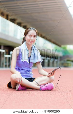 Woman listen to music and sitting on sport stadium