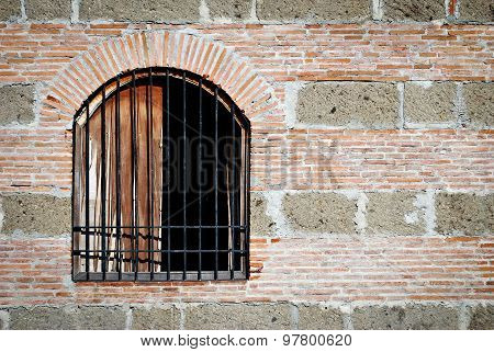 Old Barred Window on a Brick and Stone Wall