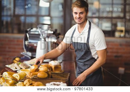Handsome waiter picking up a roll at the coffee shop