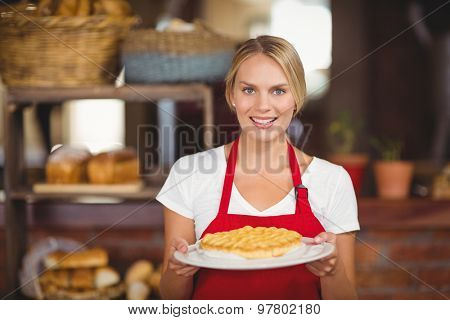 Portrait of a waitress holding a plate of cake at the coffee shop