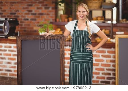 Portrait of a waitress holding a big chalkboard at the coffee shop