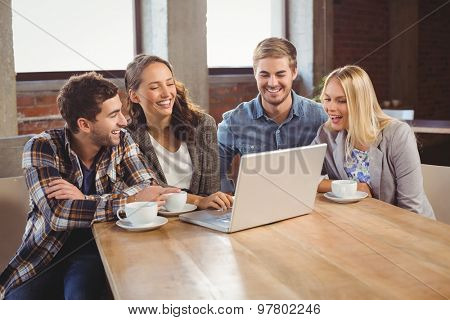 Smiling friends drinking coffee and using laptop at coffee shop