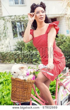 sexy woman wearing vintage dress. pin-up sitting on bicycle with some colorful flowers and a little