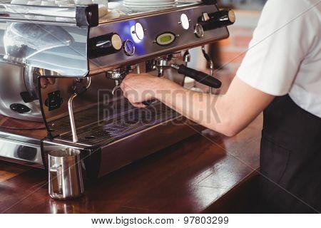 Barista preparing coffee machine at coffee shop