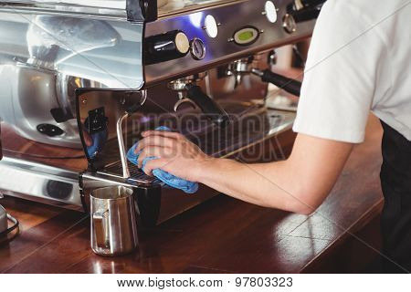 Barista cleaning coffee machine at coffee shop