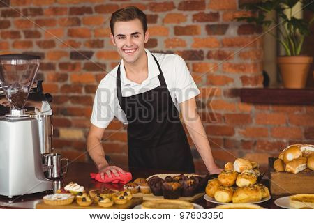 Portrait of smiling barista cleaning the counter at coffee shop