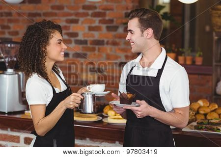 Waiter and waitress smiling at each other at coffee shop