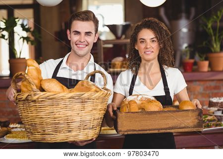 Portrait of smiling waiter and waitress holding basket full of bread rolls at coffee shop