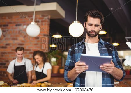 Concentrated hipster using tablet in front of working barista at coffee shop