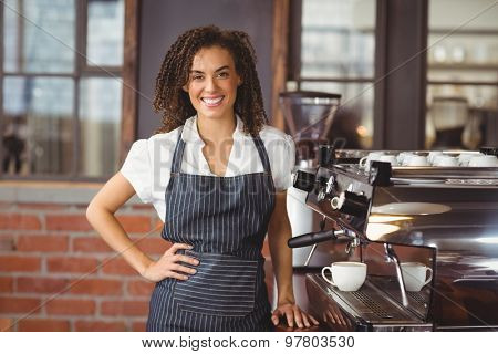 Portrait of pretty barista smiling next to coffee machine at coffee shop