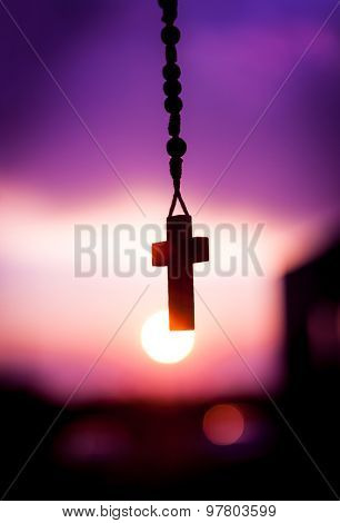 rosary beads with beautiful purple peaceful sunset , great religion or spiritual background