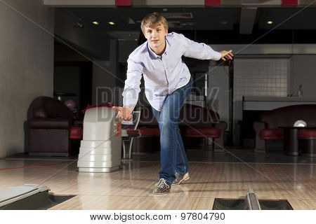 Young guy at bowling club throwing ball