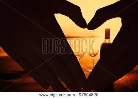 Woman making heart shape with hands against bottle of vine with two glass