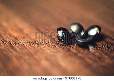 Vintage metal buttons on wood floor background