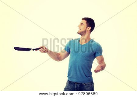 Handsome muscular man holding frying pan.